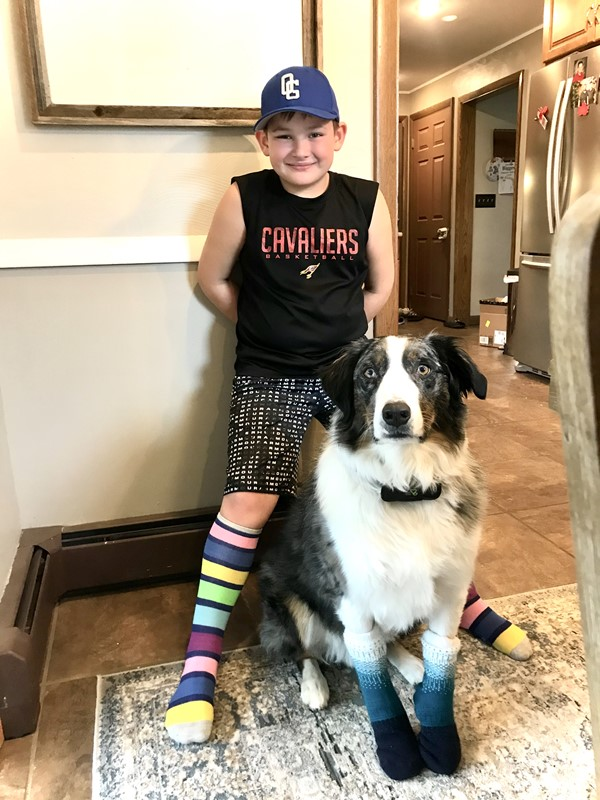 Male student and his dog wearing mismatched socks  supporting World Down Syndrome  Day.