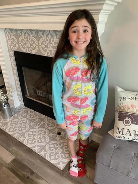 Female student wearing PJs and mismatched socks supporting World Down Syndrome  Day.