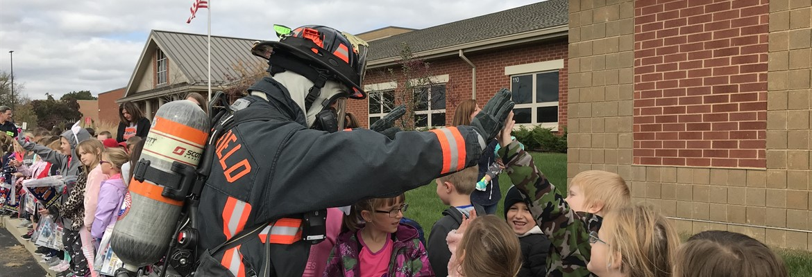 SLES students learning about fire safety. Firefighter giving students a high five.
